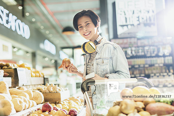 Portrait smiling young woman with headphones grocery shopping in market Portrait smiling young woman with headphones grocery shopping in market