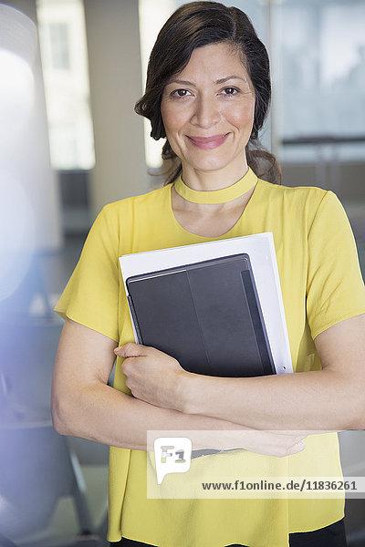 Portrait lächelnde  selbstbewusste Geschäftsfrau mit digitalem Tablett und Papierkram