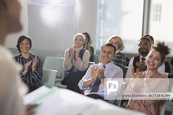 Geschäftsleute im Publikum klatschen für Konferenzredner