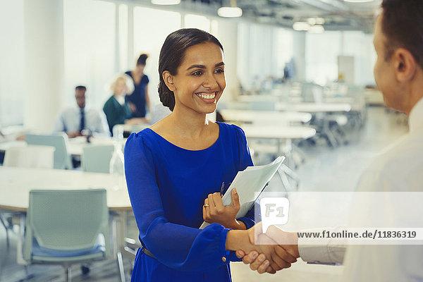 Lächelnde Geschäftsfrau beim Händeschütteln mit Geschäftsmann im Amt