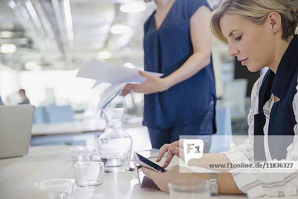 Geschäftsfrau mit digitalem Tablett im Büromeeting