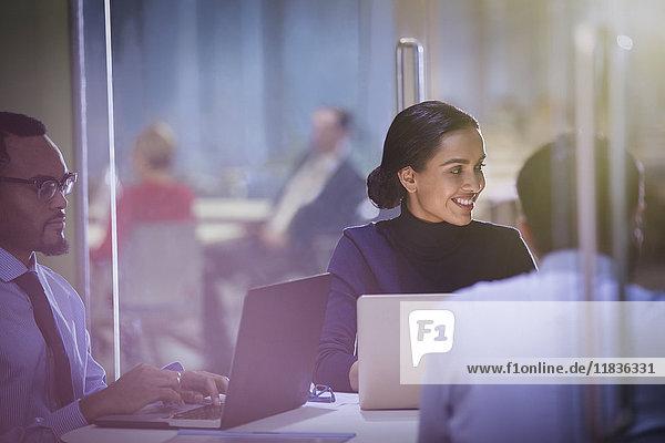 Lächelnde Geschäftsfrau am Laptop beim Zuhören im Konferenzraum Meeting
