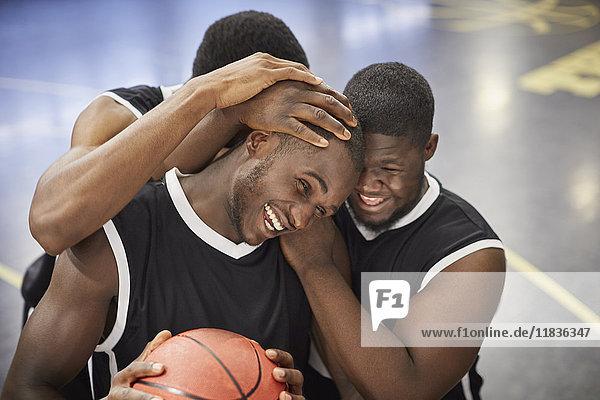 Fröhliche junge Basketballspieler umarmen und feiern nach dem Sieg