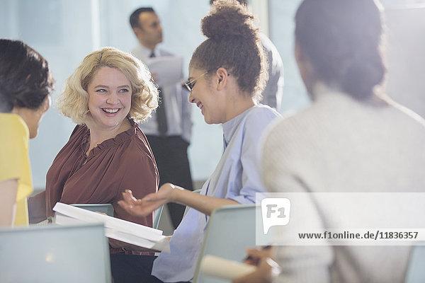 Lächelnde Geschäftsfrauen diskutieren Papierkram im Konferenzpublikum