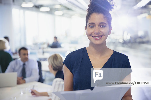 Portrait lächelnde  selbstbewusste junge Geschäftsfrau mit Papierkram im Büro