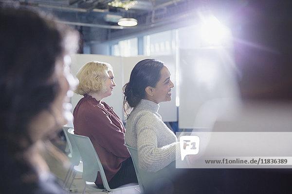 Lächelnde Geschäftsfrauen beim Zuhören im Konferenzpublikum