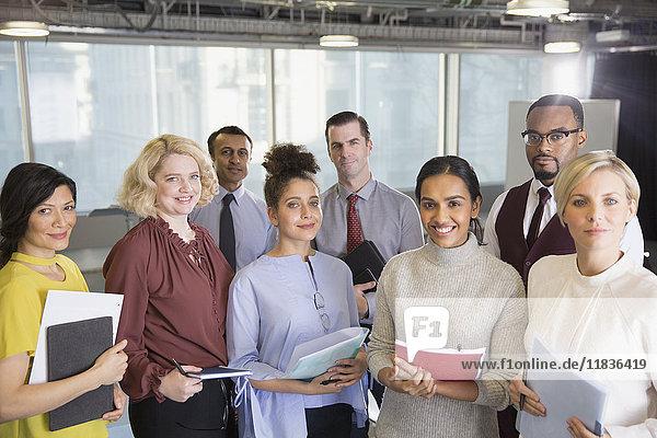 Portrait lächelnde Geschäftsleute mit Papierkram im Konferenzraum