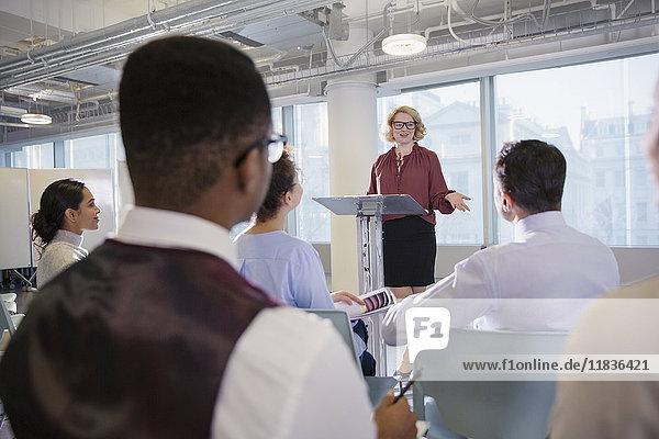 Geschäftsfrau bei Podiumsdiskussionspräsentation