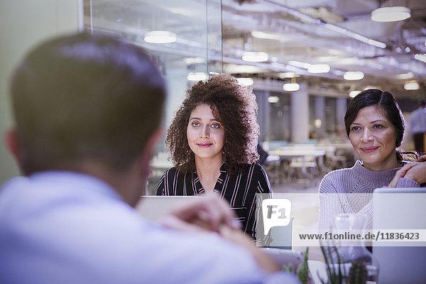Geschäftsfrauen hören im Konferenzraum zu