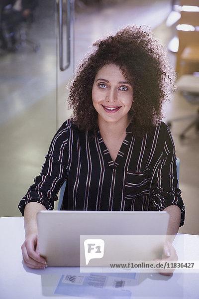 Portrait lächelnde  selbstbewusste Geschäftsfrau bei der Arbeit am Laptop