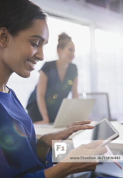 Lächelnde Geschäftsfrau mit digitalem Tablett in Konferenzraumbesprechung