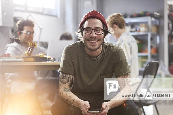 Portrait lächelnder  selbstbewusster Designer mit Handy