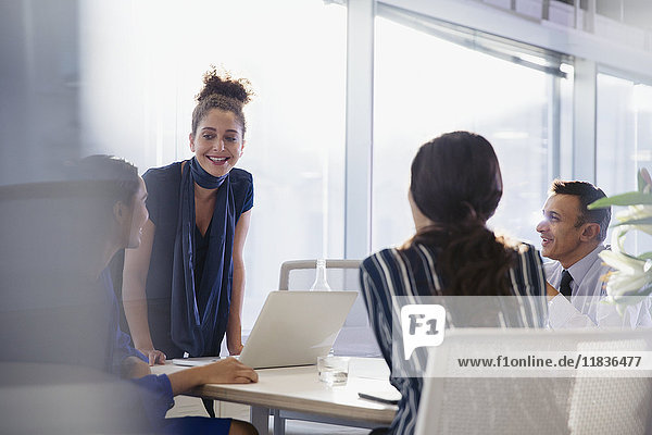 Businesswoman at laptop leading conference room meeting