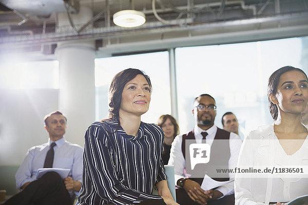 Aufmerksame Geschäftsfrau beim Zuhören im Konferenzpublikum