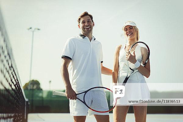 Portrait lächelnde  selbstbewusste Tennisspieler mit Tennisschlägern auf sonnigem Tennisplatz
