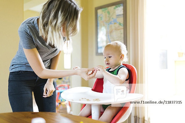 Mother feeding son (12-17 months) with breakfast cereals