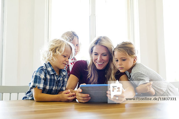 Mother and children (4-5  6-7  8-9) with digital tablet