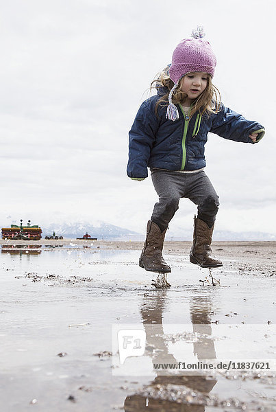 Little girl (4-5) jumping in puddle