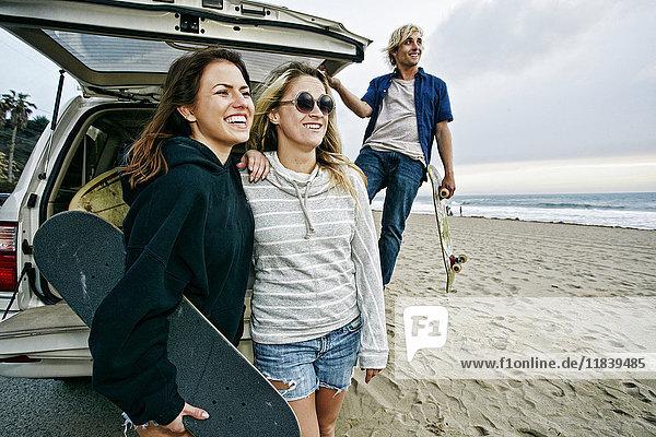 Caucasian friends near car hatch at beach holding skateboards
