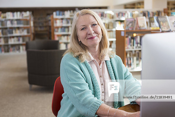 Smiling Caucasian woman using computer in library