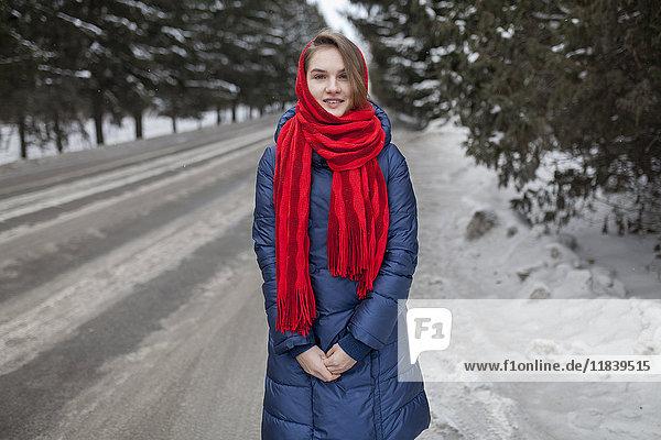 Smiling Caucasian woman standing near road in winter