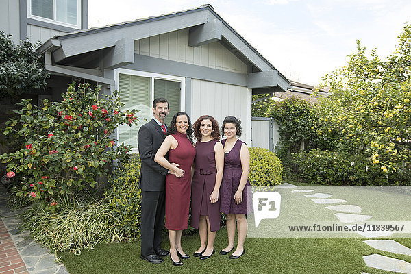 Parents and daughters posing near house