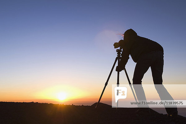 Silhouette of Mixed Race photographer with camera at sunset