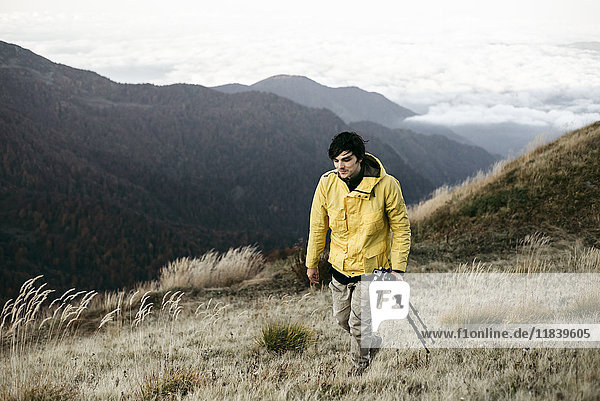 Caucasian man carrying tripod in remote mountain landscape