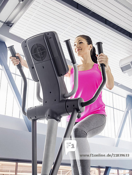 Caucasian woman using elliptical machine in gymnasium