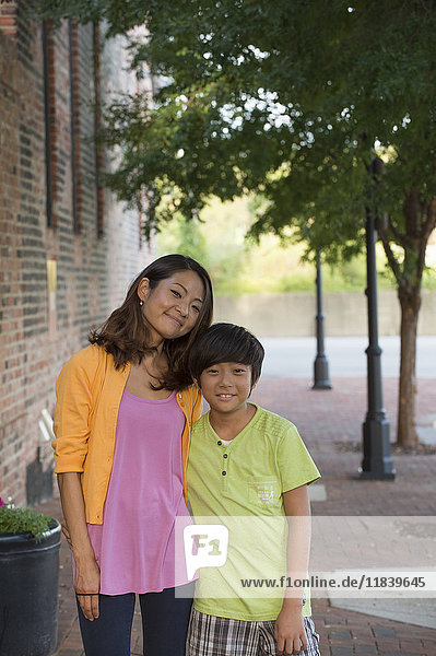 Portrait of Asian mother and son standing on sidewalk