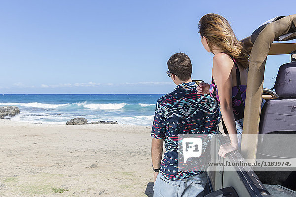 Couple leaning on convertible car at beach