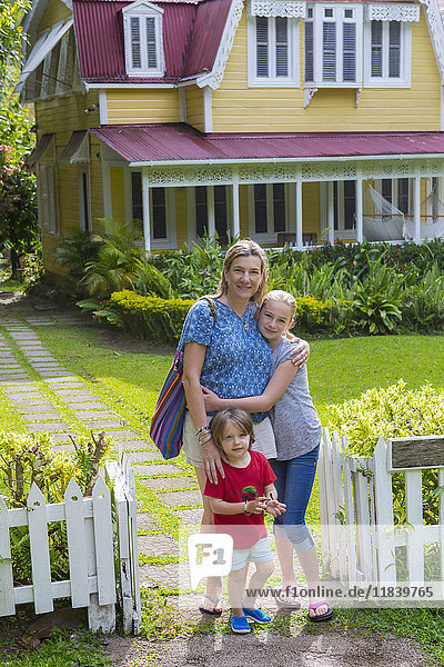 Caucasian mother with son and daughter in front view house