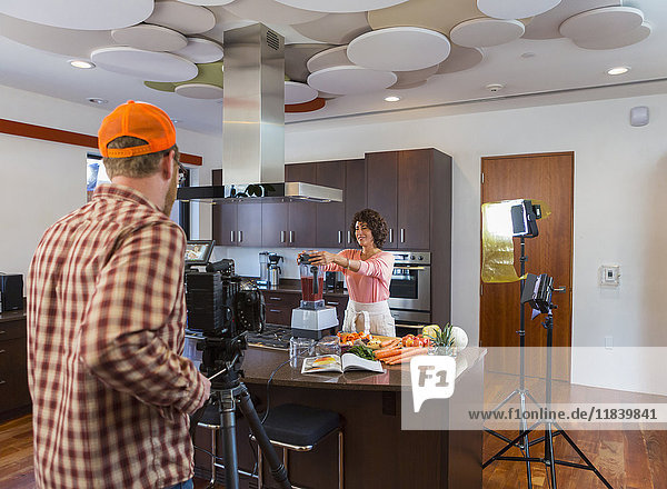 Cameraman recording woman preparing smoothie in domestic kitchen