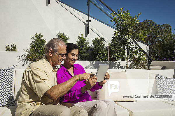 Older couple using digital tablet on modern backyard patio