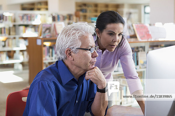 Older Hispanic woman helping man using computer in library