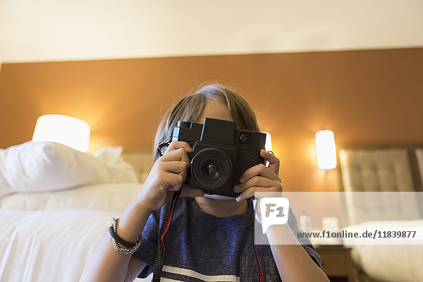 Caucasian boy photographing with camera in hotel room