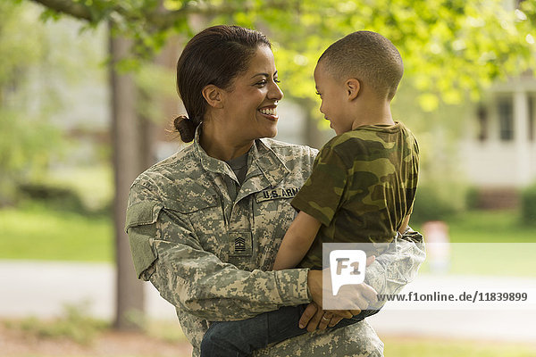 African American soldier mother carrying son