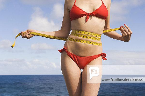 Mixed Race woman wearing bikini measuring waist near ocean