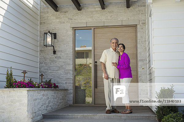 Older couple posing on front stoop of house