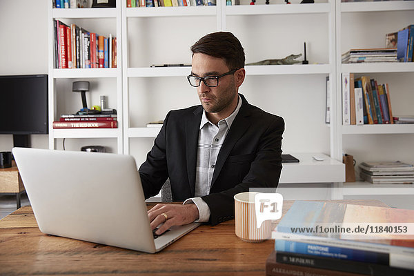Caucasian businessman using laptop in home office