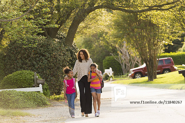 Mother walking in street with daughters wearing backpacks