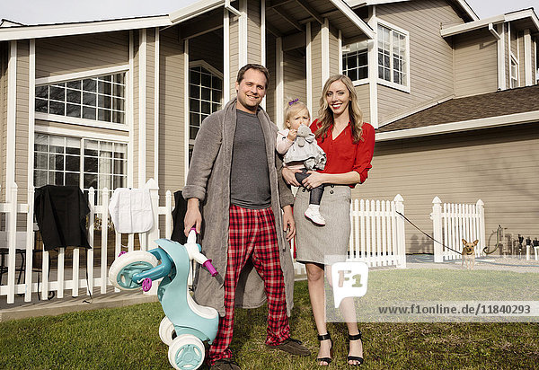 Caucasian couple posing on lawn with baby daughter