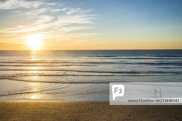 Couple in backlight walking at sunset  Del Mar  California  United States of America  North America