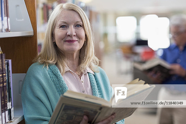 Smiling Caucasian woman holding book in library