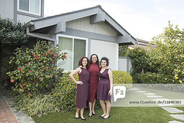 Mother and daughters posing near house