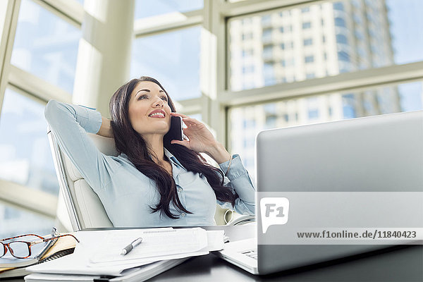 Caucasian businesswoman talking on cell phone