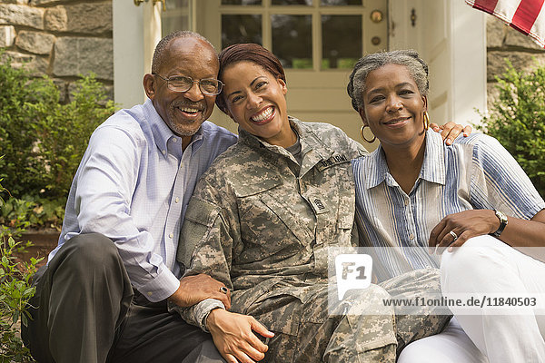 Portrait of soldier sitting on front stoop with parents