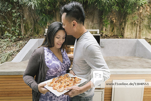 Man kissing forehead of expectant mother near grille