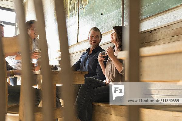 Freunde unterhalten sich in einer Brauereikneipe hinter einem Stuhl