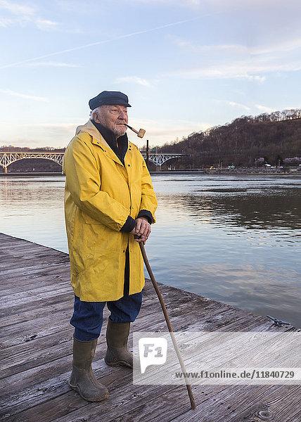Older Caucasian fisherman standing on dock